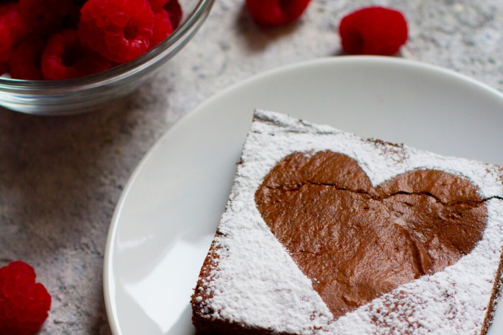 A brownie with a powdered sugar heart on a plate beside a bowl of raspberries