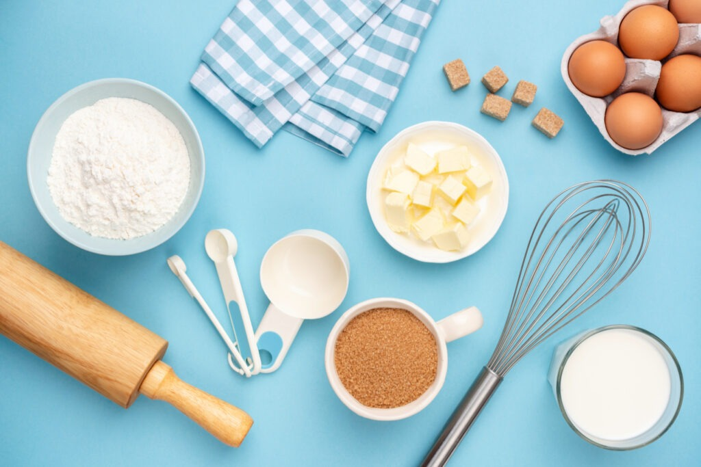 Various baking ingredients and tools on a blue background