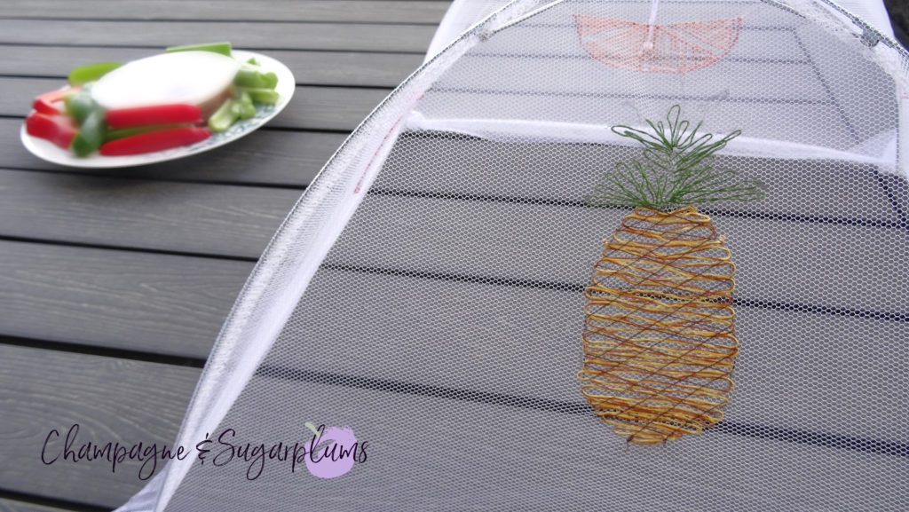 A summer food tent with embroidered fruits on a picnic table by Champagne and Sugarplums