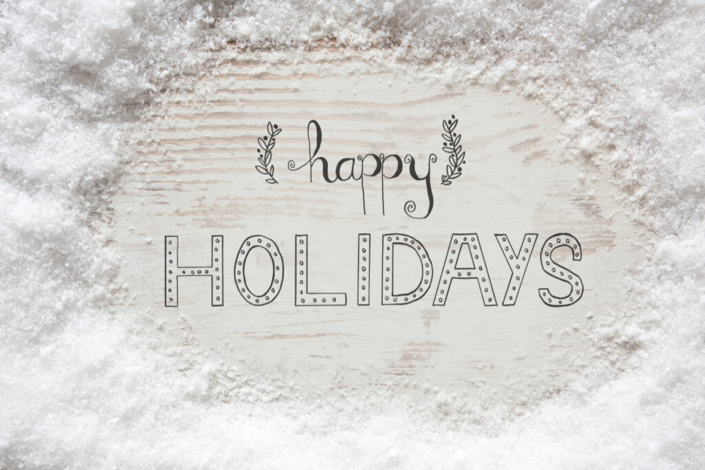 Happy Holidays written on a white background surrounded by snow