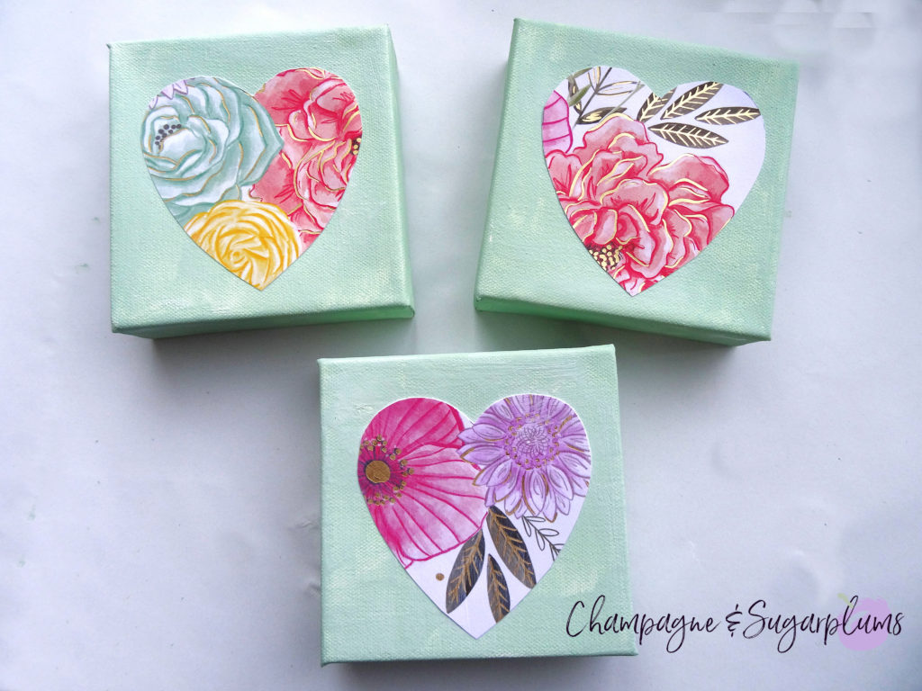 Three completed floral triptych canvases with paper hearts on a white background by Champagne and Sugarplums