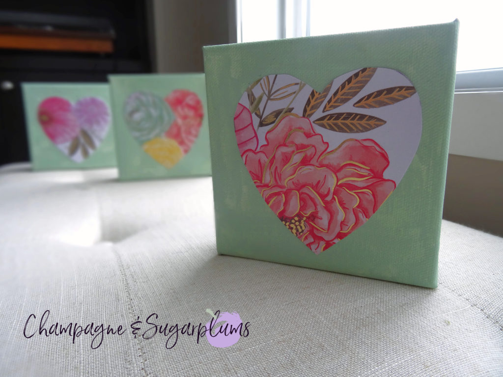 Three completed floral triptych canvases with paper hearts by a window by Champagne and Sugarplums