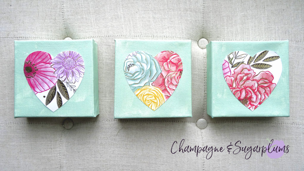 Three completed floral triptych canvases with paper hearts on a bench by Champagne and Sugarplums