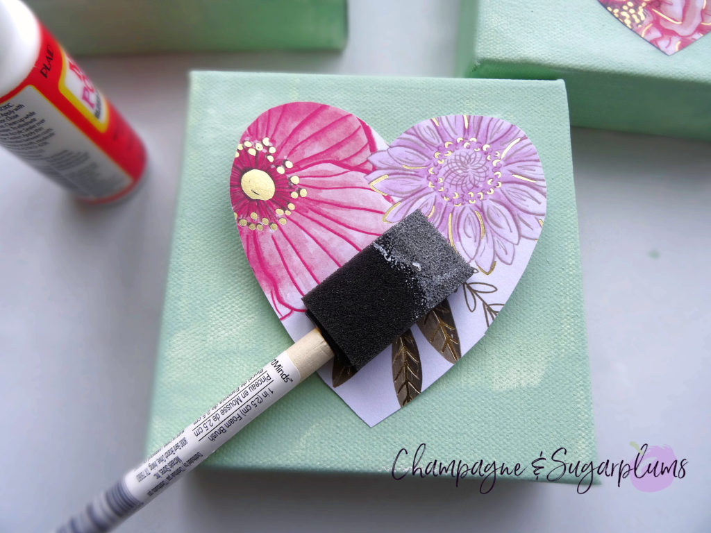 Gluing a paper heart onto a canvas with a foam brush by Champagne and Sugarplums