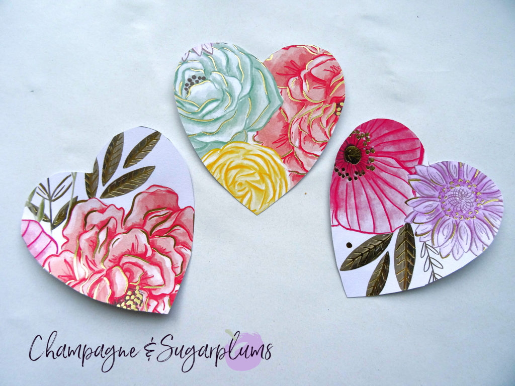 Three hearts cut from floral paper on a white background by Champagne and Sugarplums