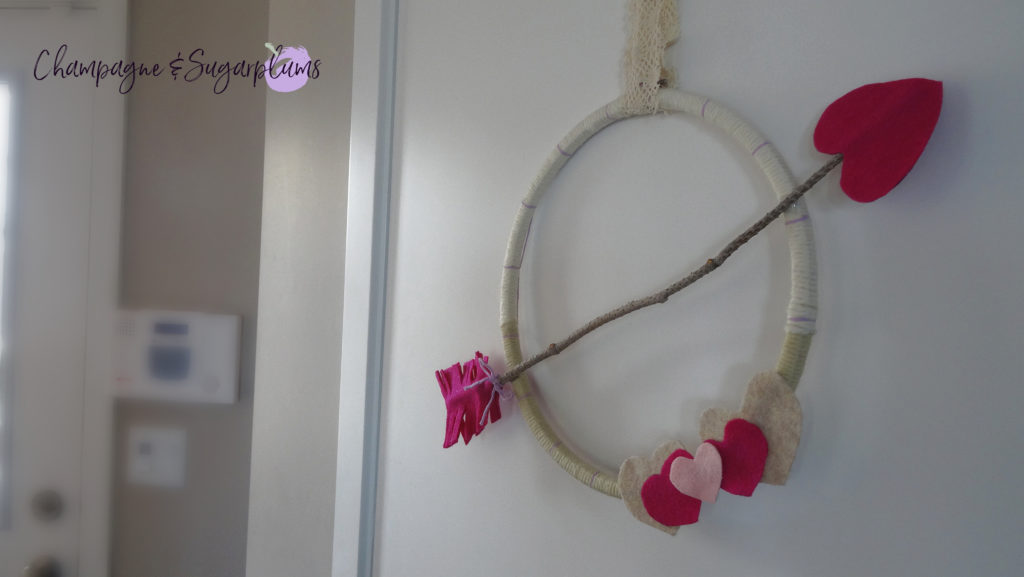 Completed Valentine's Day Wreath hanging on a door by Champagne and Sugarplums