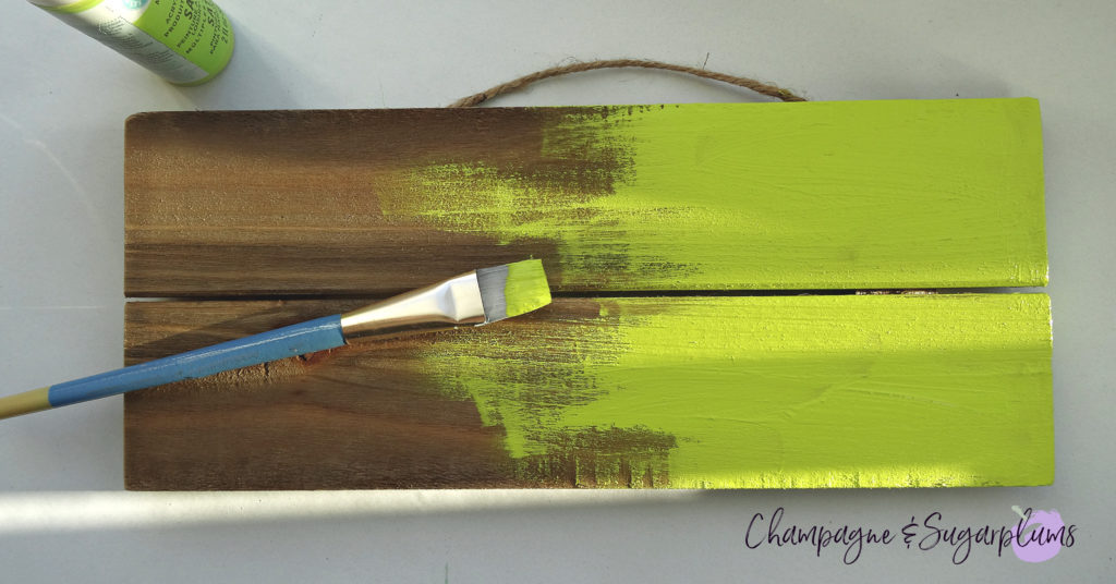 Painting a wood plank bright green for a lucky signboard by Champagne and Sugarplums