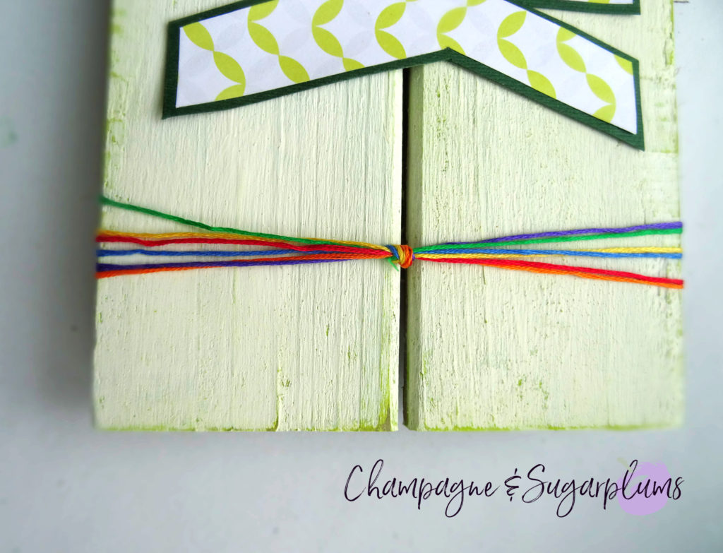 A rainbow of embroidery thread tied around the end of a wood plank by Champagne and Sugarplums