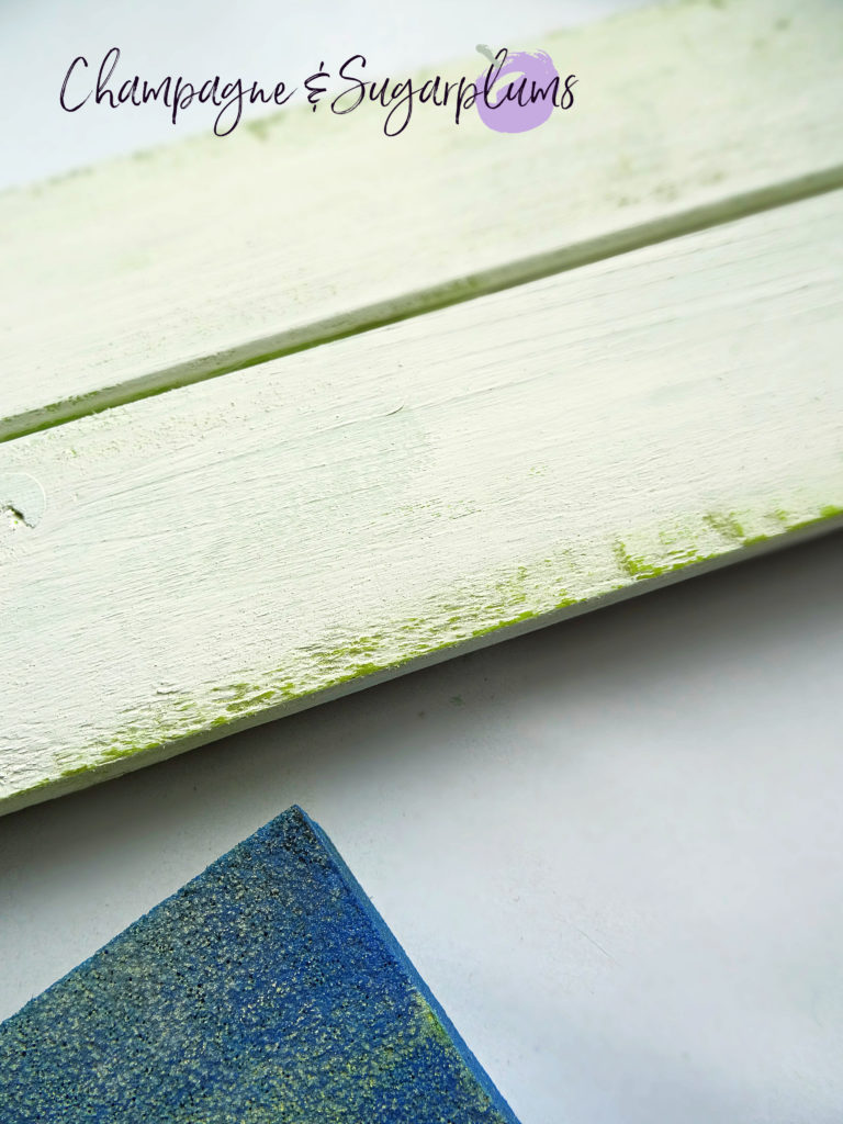 Sanding white paint to reveal green paint underneath on a wood plank by Champagne and Sugarplums