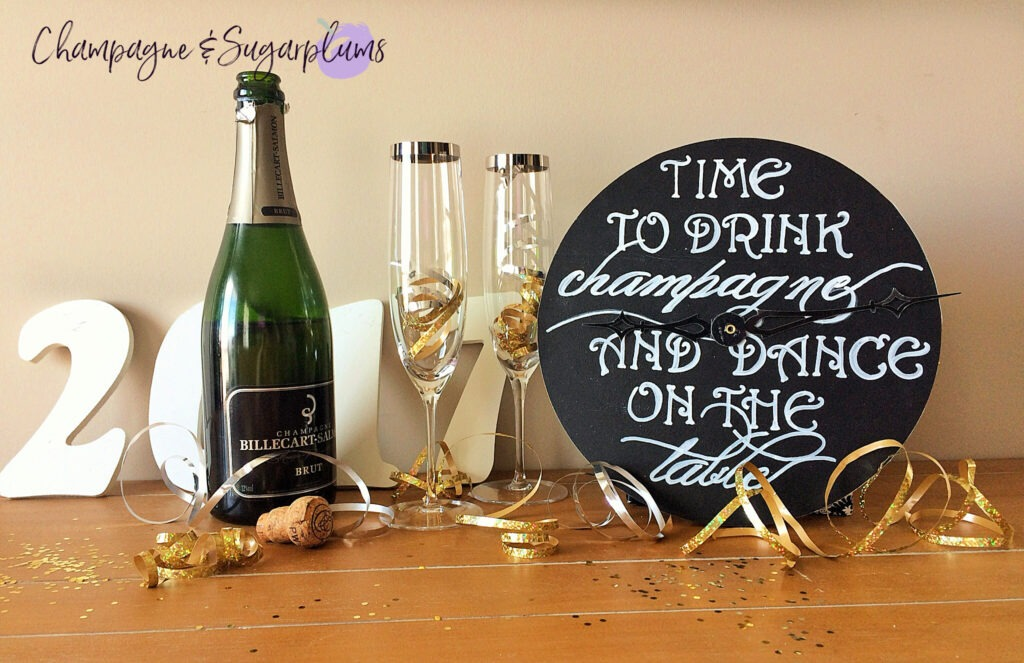 Countdown clock on a table with champagne glasses, bottle, ribbon and glitter by Champagne and Sugarplums