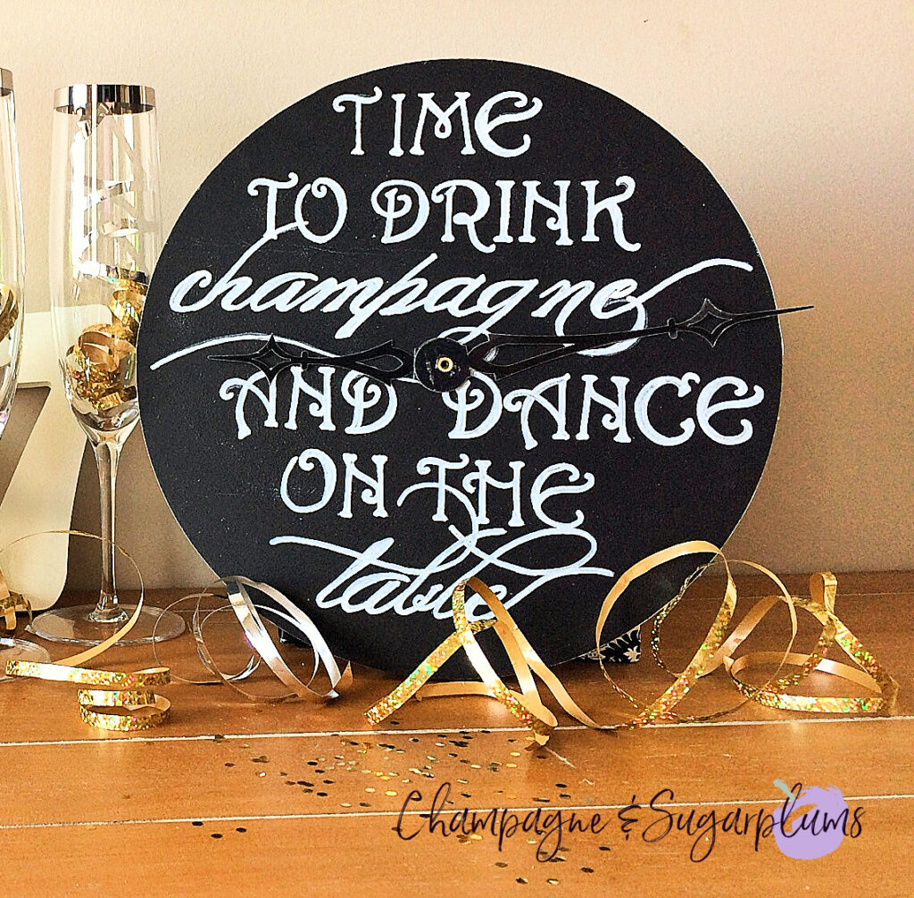 Countdown clock on a table with champagne glasses, ribbon and glitter by Champagne and Sugarplums