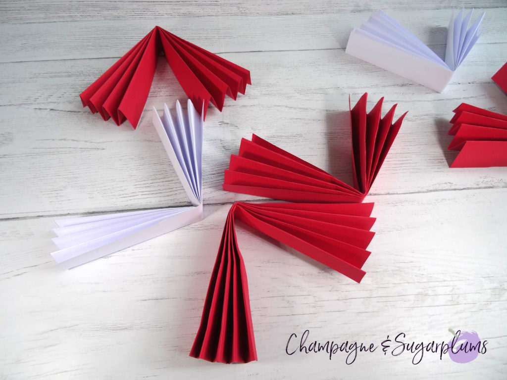 Red and white paper accordions being folded half by Champagne and Sugarplums