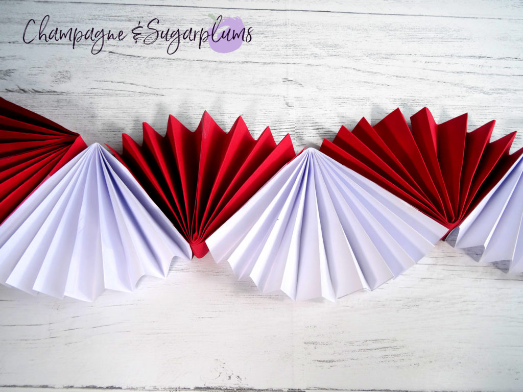 Red and white paper accordions being taped together by Champagne and Sugarplums