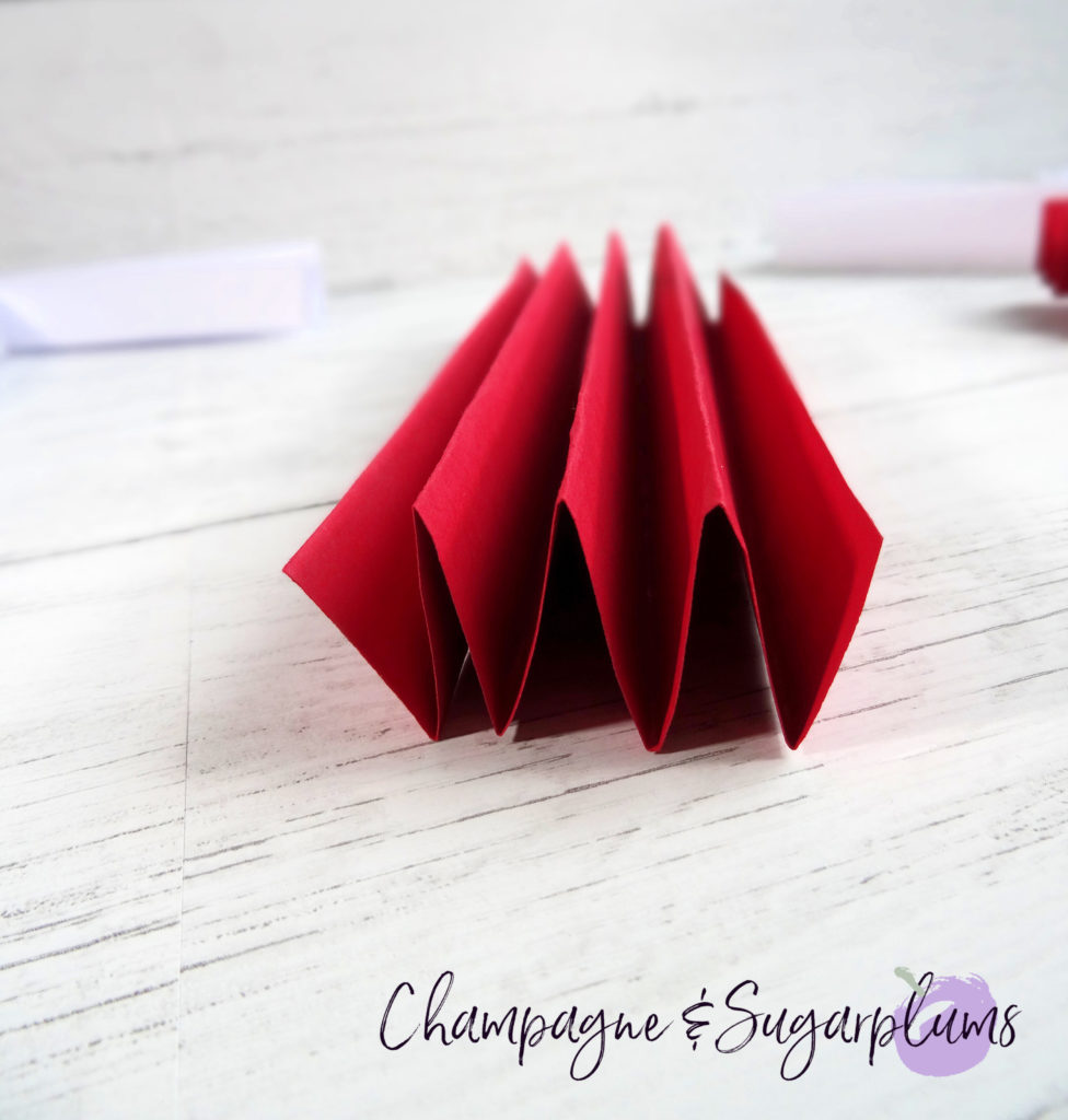 Red paper being folded it an accordion shape by Champagne and Sugarplums