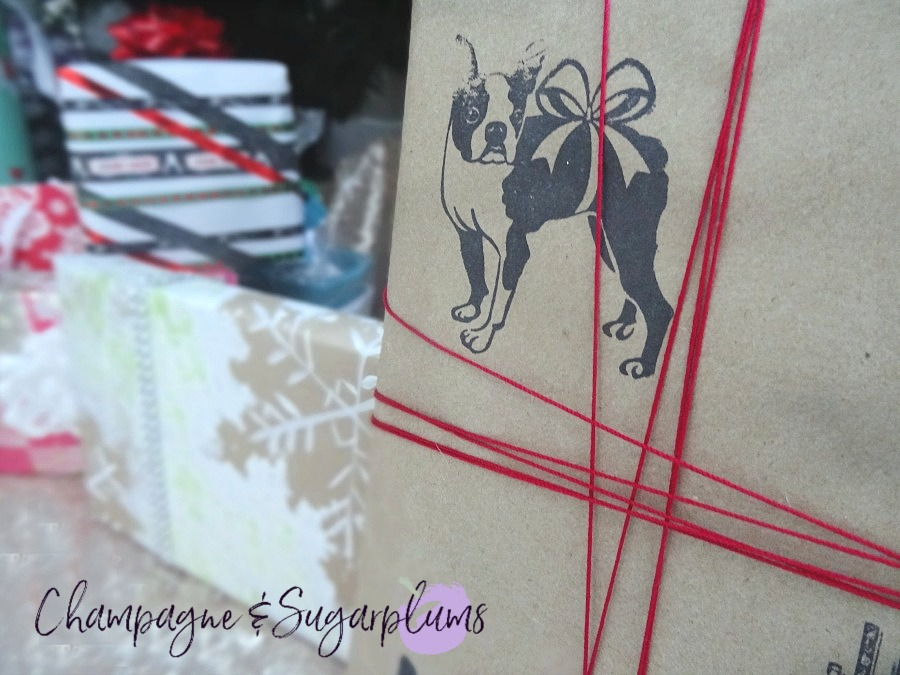 A collection of gifts wrapped in DIY holiday wrapping paper under a tree by Champagne and Sugarplums