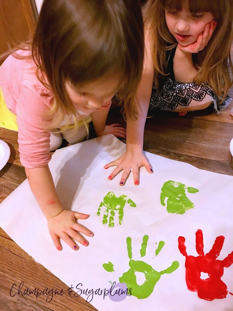 Two young girls putting their handprints onto white paper with red and green paint by Champagne and Sugarplums