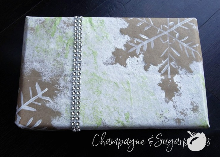 A gift wrapped in snowflake printed holiday wrapping paper with a diamond ribbon by Champagne and Sugarplums