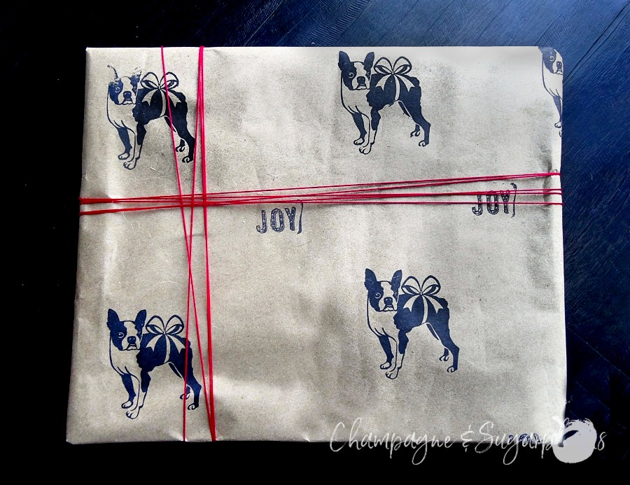 A gift wrapped in butcher paper stamped with Boston terriers with red twine around it by Champagne and Sugarplums