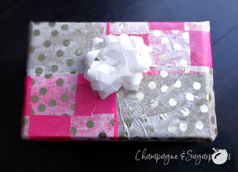 A gift wrapped in pink and gold polka dot patterned holiday wrapping paper  by Champagne and Sugarplums