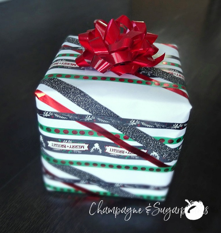 A gift wrapped in lines of patterned Washi tape with a red bow by Champagne and Sugarplums