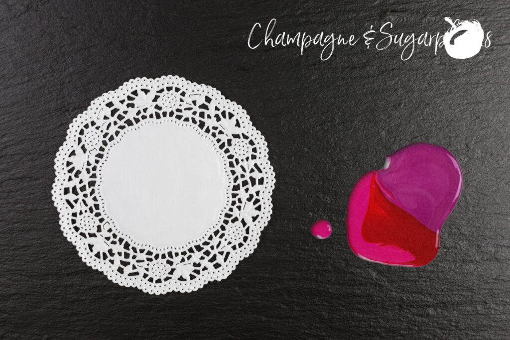 White doily and pink and red paint on a dark background by Champagne and Sugarplums