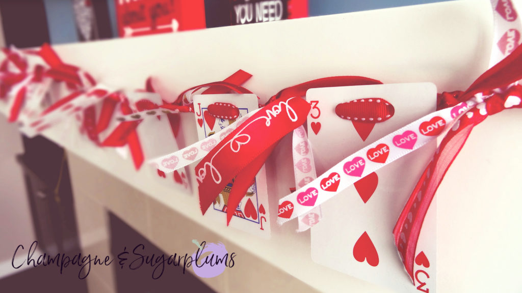Heart cards garland hanging on a mantel by Champagne and Sugarplums