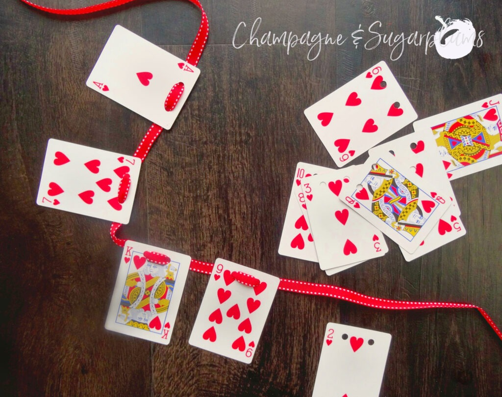 Playing cards being threaded onto ribbon by Champagne and Sugarplums