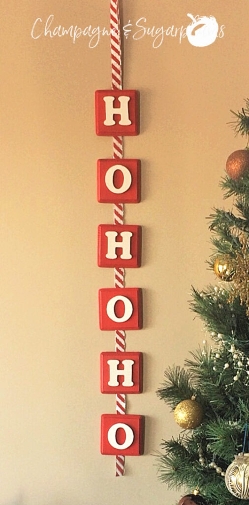 Christmas banner hanging on a wall beside a decorated tree by Champagne and Sugarplums
