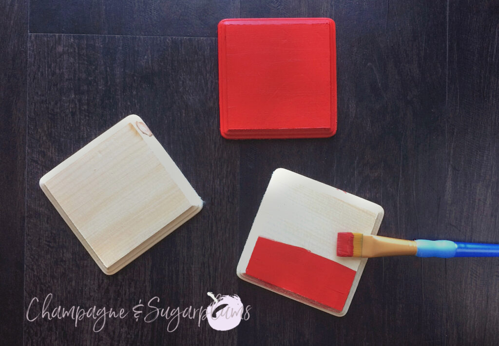 Three wood squares being painted red by Champagne and Sugarplums