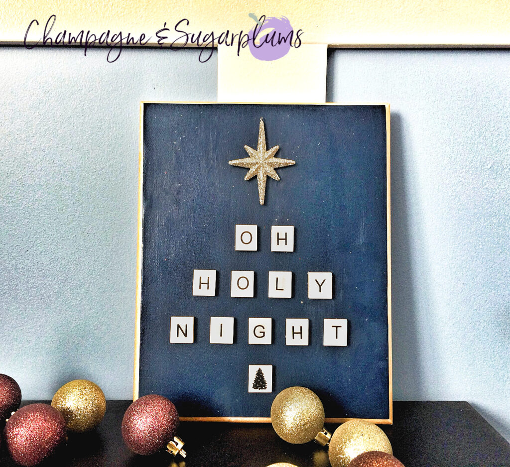 Letter tile plaque on a table with a blue wall with mini ornaments by Champagne and Sugarplums