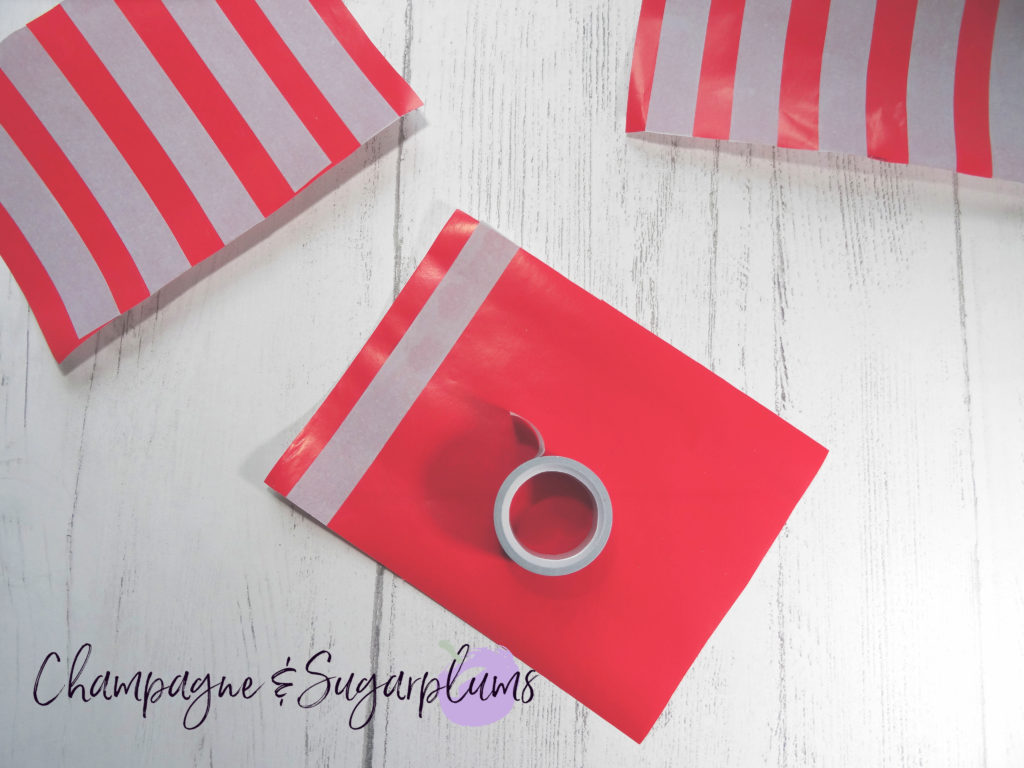 Adding tape stripes to red paper by Champagne and Sugarplums