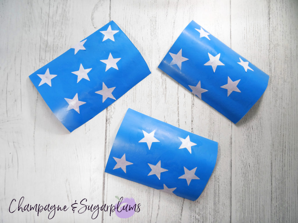 Adding star stickers to blue paper by Champagne and Sugarplums