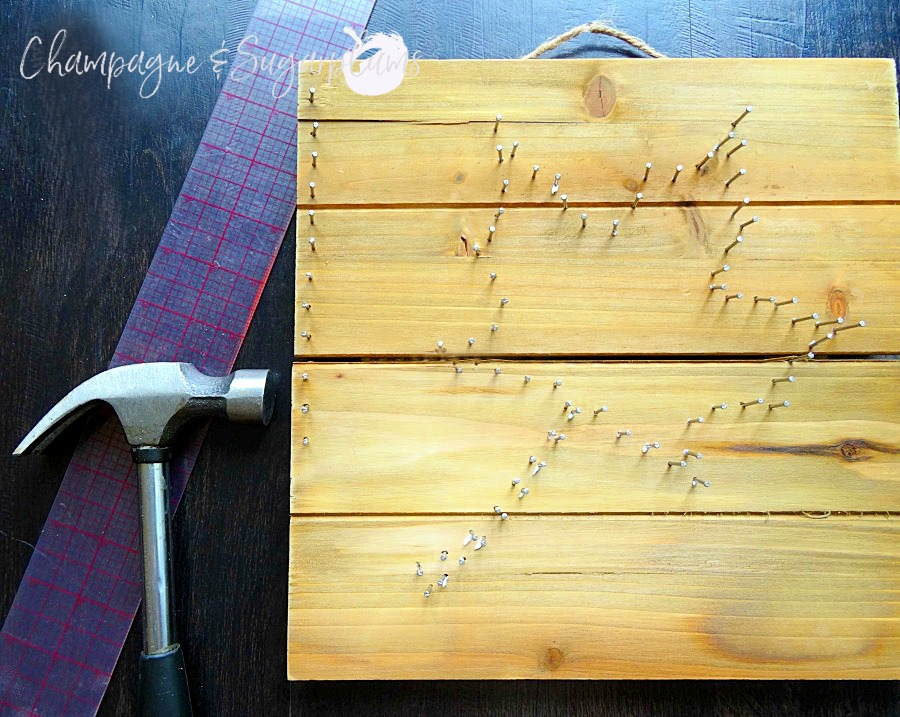 Hammering nails into a wood board by Champagne and Sugarplums