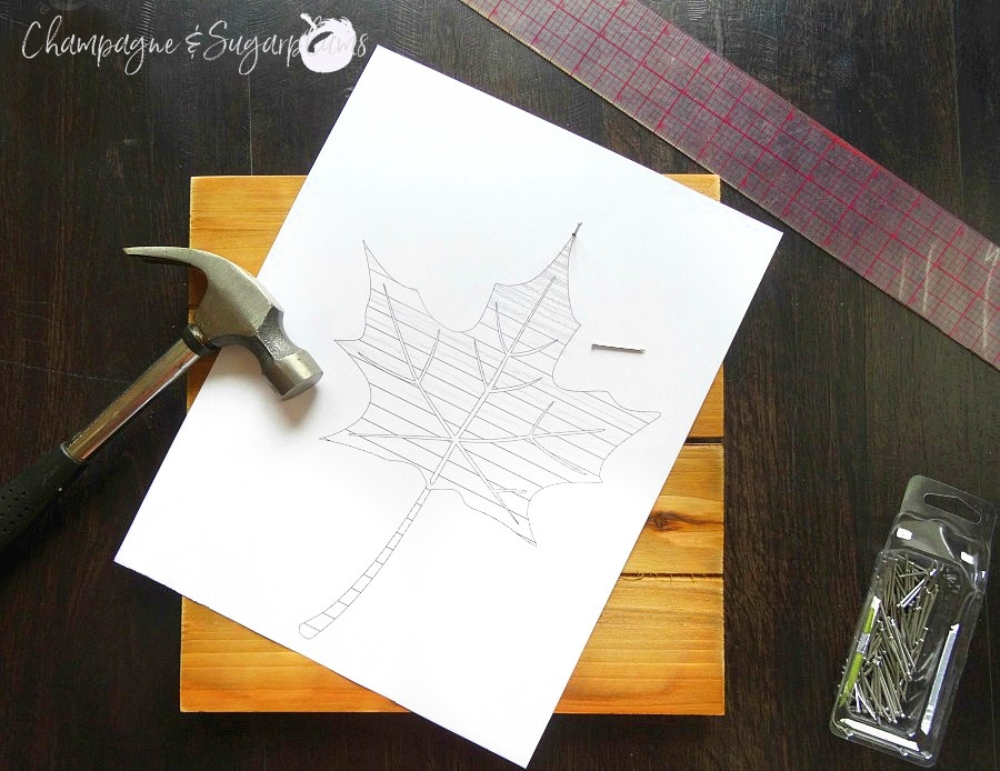Paper leaf template nailed to a wood board by Champagne and Sugarplums