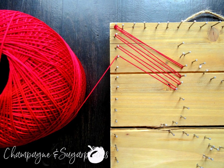 Adding red thread around nails in wood by Champagne and Sugarplums