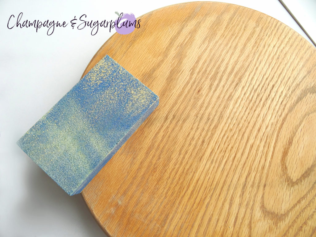 Wood board being sanded by Champagne and Sugarplums