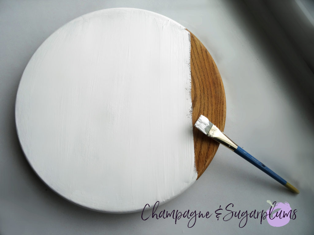 Wood circle being painted white by Champagne and Sugarplums