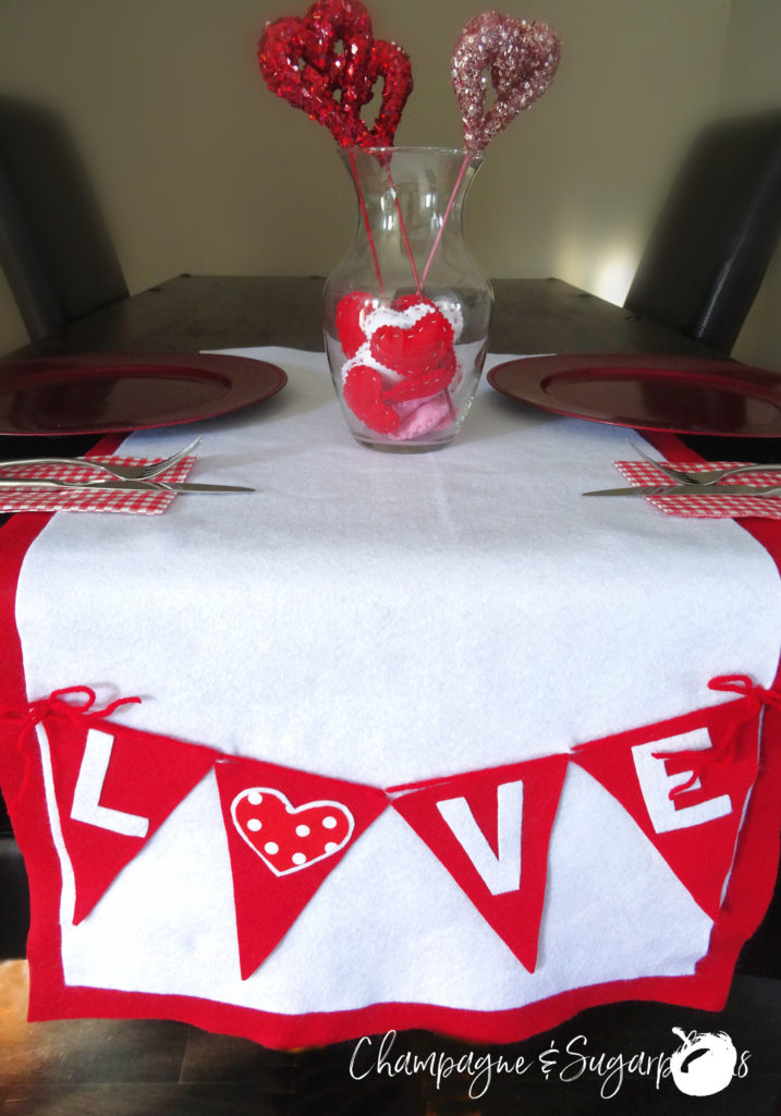 Love table runner on a dark table, with red plates and vase with hearts by Champagne and Sugarplums