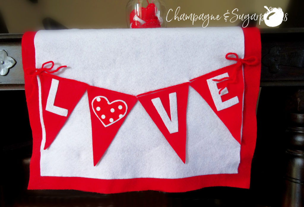 Love table runner on a dark table, close-up by Champagne and Sugarplums