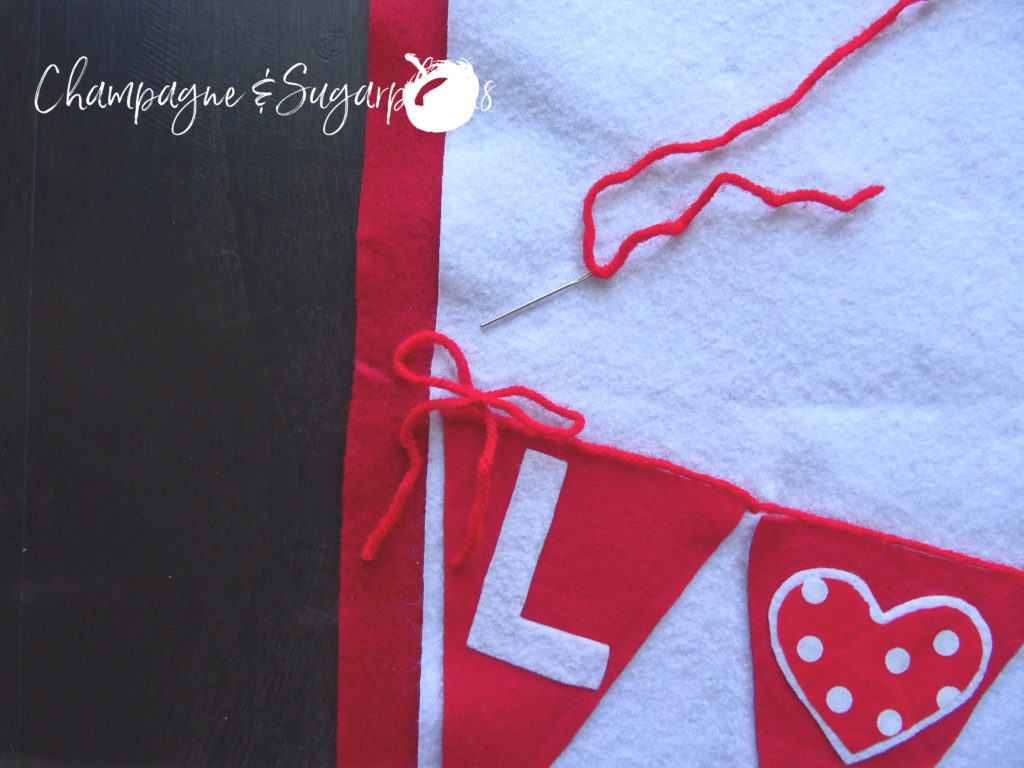 Red yarn bow attached to the corner of a felt flag on a Love table runner by Champagne and Sugarplums