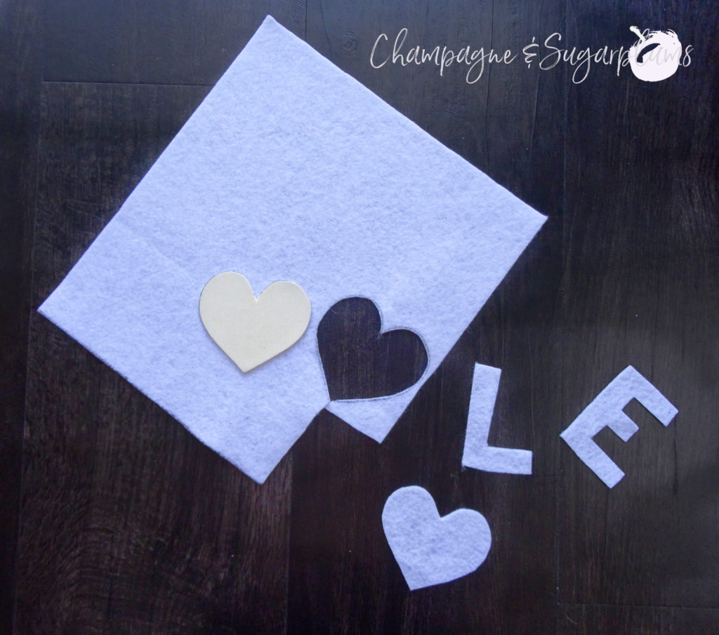 The letters L and E and a heart cut from white felt by Champagne and Sugarplums