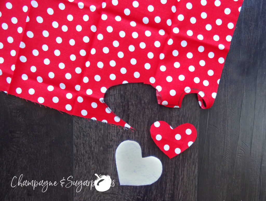 A heart cut from red and white polka dot fabric by Champagne and Sugarplums