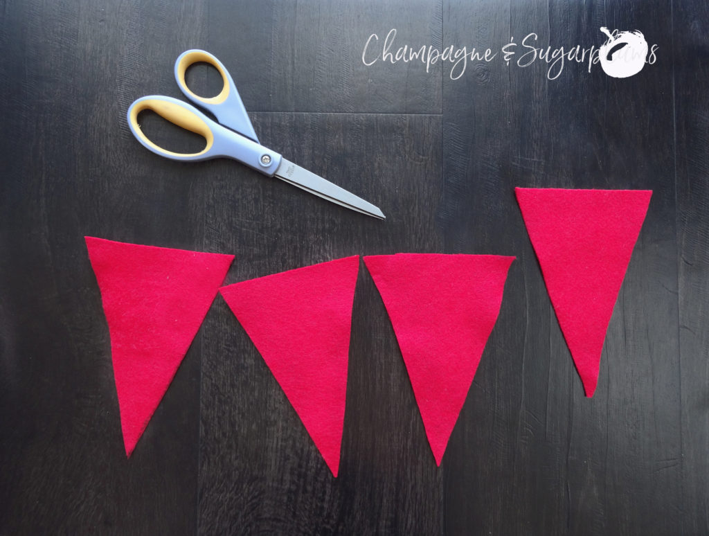 Four red felt flags with a pair of scissors for a Love table runner by Champagne and Sugarplums