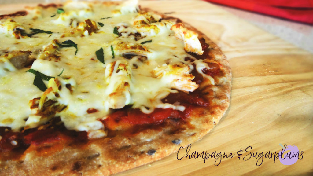 Mango chicken pizza on a wood board by Champagne and Sugarplums