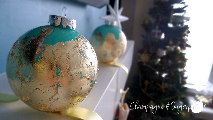 Ornament stocking holders on a white mantel surrounded by mini gold and brown ornaments with Christmas tree in the background by Champagne and Sugarplums
