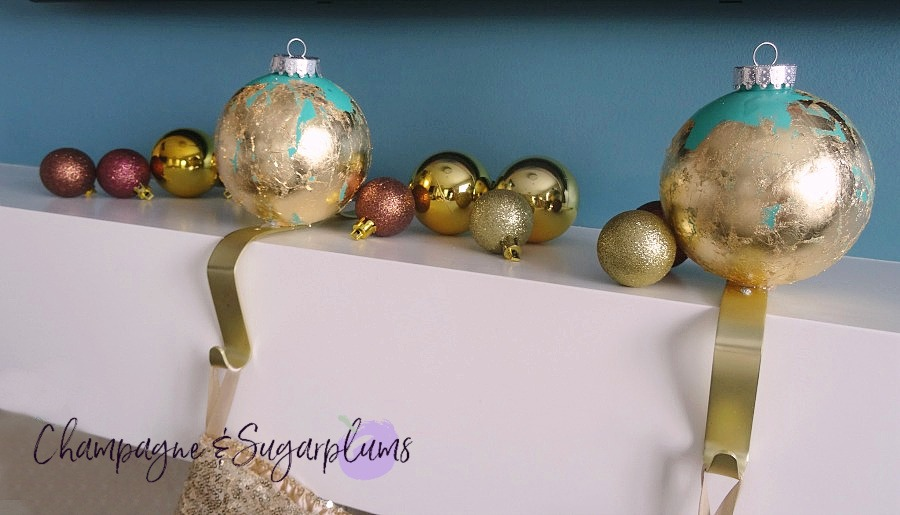 Ornament stocking holders on a white mantel surrounded by mini gold and brown ornaments by Champagne and Sugarplums