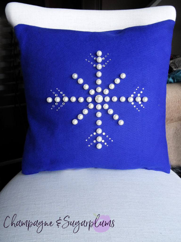 Snowflake pillow cover on a white chair by Champagne and Sugarplums