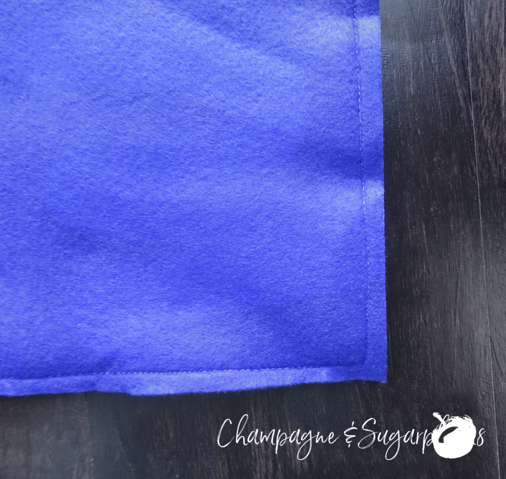 The corner of two pieces of royal blue felt sewn together by Champagne and Sugarplums