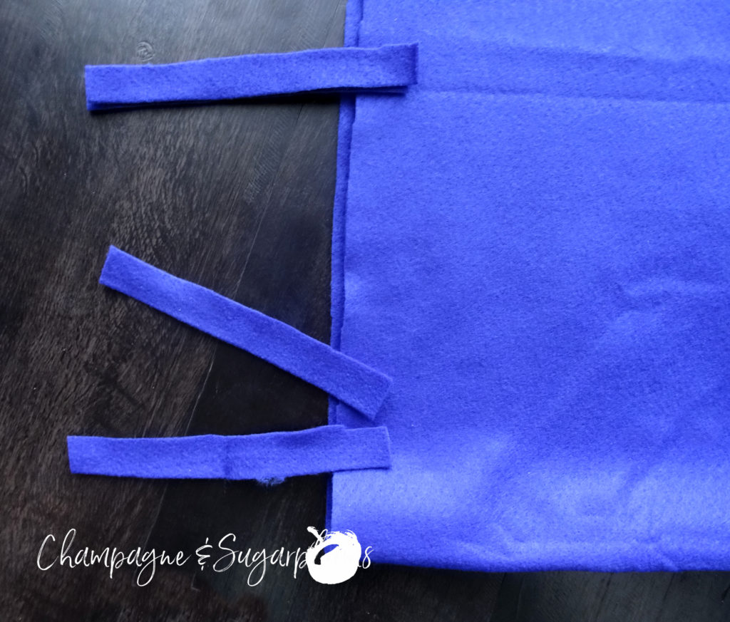 Strips of royal blue felt being sewn to the a pillow cover by Champagne and Sugarplums