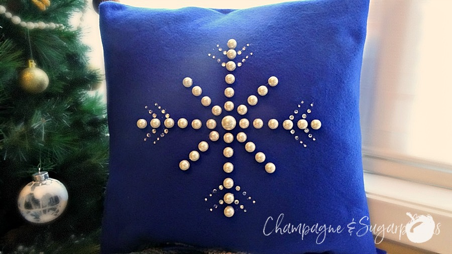 Snowflake pillow cover on a bench beside a Christmas tree by Champagne and Sugarplums
